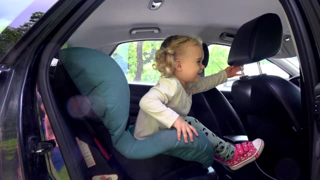 Adorable toddler girl wave hand and jump off car safety seat chair video