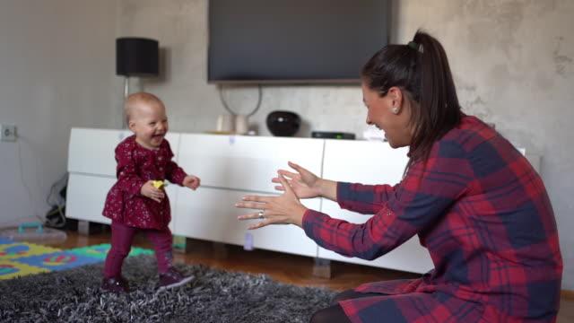 vídeos y material grabado en eventos de stock de adorable niño apenas mantener el equilibrio en sus primeros pasos a su madre - principios