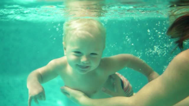 Adorable toddler is swimming under the water in the swimming pool together with his mother. An underwater shot. Slowmotion