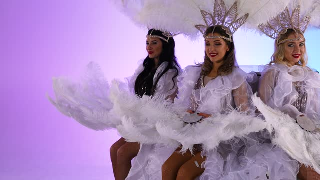 vídeos de stock e filmes b-roll de adorable women in white snow queen costumes and feather headdresses blow glitter and have fun. dancers posing against a light blue studio background. close up. slow motion - bolo rainha