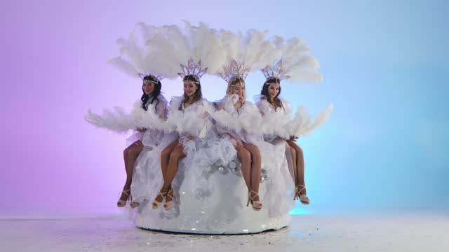 vídeos de stock e filmes b-roll de adorable women in white snow queen costumes and feather headdresses blow glitter and have fun sitting on a big cake. dancers posing against a light blue studio background. slow motion - bolo rainha