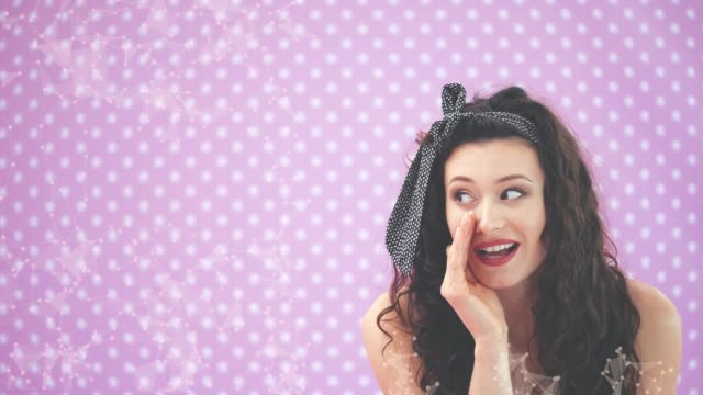 Adorable young girl in black polka-dots dress, leaning to the camera, whispering, pointing her finger to the side, showing tongue.