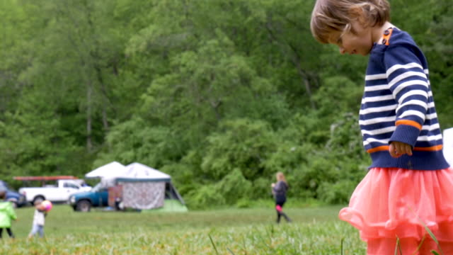 Adorable young girl looking down at the grass playing outside video