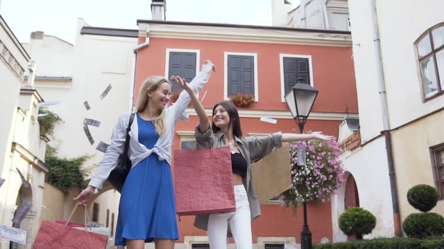 Adorable young stylish women throwing up a lot of money and having fun in the city yard