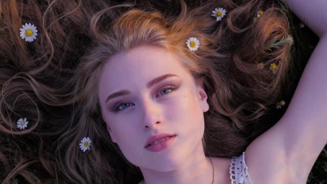 愛らしい若い女性は緑の芝生の上に横たがあり、カメラを見上げる - 自生点の映像素材/bロール