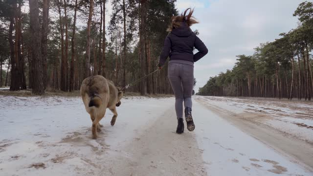 Adorable young woman running with her cute dog in winter autumn forest in cold sunny day
