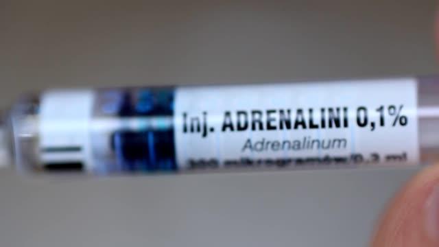adrenalina a iniezione siringa macro girato - adrenalina video stock e b–roll