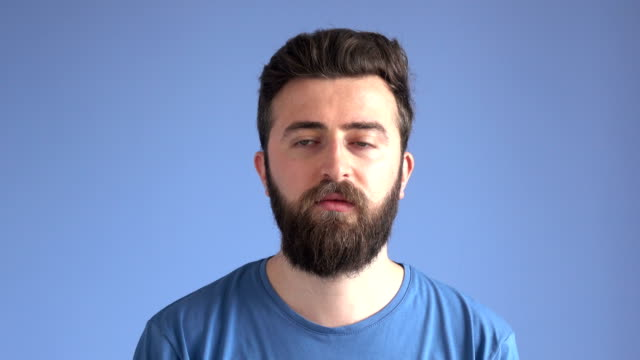 Adult Arrogant Man Making Facial Expression On Blue Background 4K video of adult man with blue eyes,brown hair and beard making face of arrogance. The background is blue and model is wearing a blue shirt. vanity stock videos & royalty-free footage