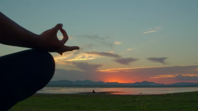 Adult asian sport woman yoga ,meditating in Lotus Pose pose on the beach when sunset.4k dci footage.light leaking of sun flare.Silhouette shot. Adult asian sport woman yoga ,meditating in Lotus Pose pose on the beach when sunset.4k dci footage.light leaking of sun flare.Silhouette shot. lotus position stock videos & royalty-free footage