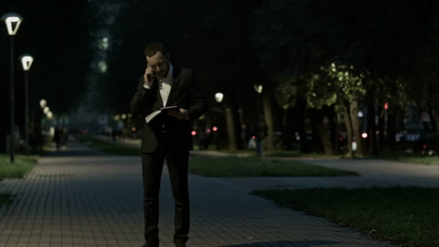 Adult bearded business man talking on cell phone while standing in the city street, business man have conversation, stylish hipster in suit using cellphone video