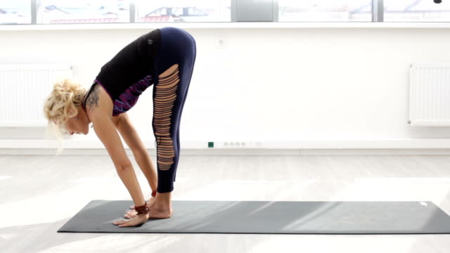 adult blonde woman performing the beginning of morning yoga complex, doing inclination to the feet - posizione corretta video stock e b–roll