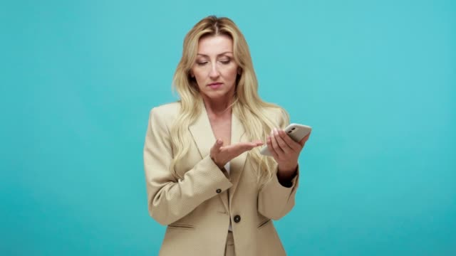 Adult business woman with blond hair watching photos on smartphone, scrolling web pages with surprised shocked face, blogging