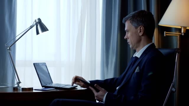 vuxen affärsman med telefon och laptop - kostym sida bildbanksvideor och videomaterial från bakom kulisserna