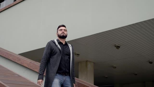 vidéos et rushes de homme d'affaires adulte portant des vêtements de style décontracté abaisse sur les escaliers du bâtiment à l'extérieur dans la journée d'automne - abaisser