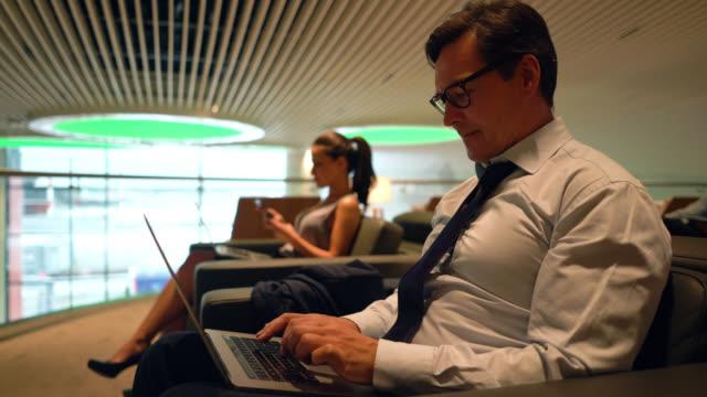 stockvideo's en b-roll-footage met volwassen zakenman werkt op zijn laptop in de vip-lounge op de luchthaven - vliegveld vertrekhal