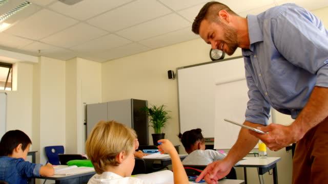 stockvideo's en b-roll-footage met volwassen kaukasische mannelijke onderwijzer helpen scholier in de klas op school 4k - schooljongen