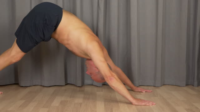 Adult caucasian man doing yoga cat exercise at living room indoors. Profile locked shot. video