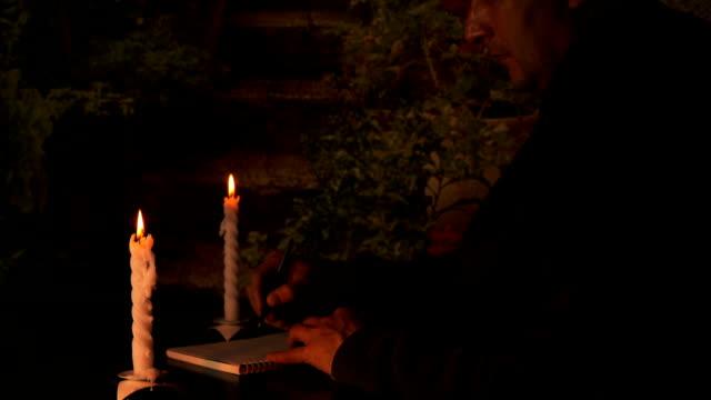 vuxen kaukasiska man teckning av pennan i anteckningsboken. levande ljus lyser upp hans ansikte. affärsman rita bisness plan på bok. natt sidovy av sitter vid bordet män. - linjerat papper bakgrund bildbanksvideor och videomaterial från bakom kulisserna