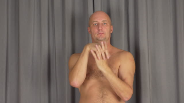Adult caucasian man warms up his palms fingers. Turn hands, rotates arms. video