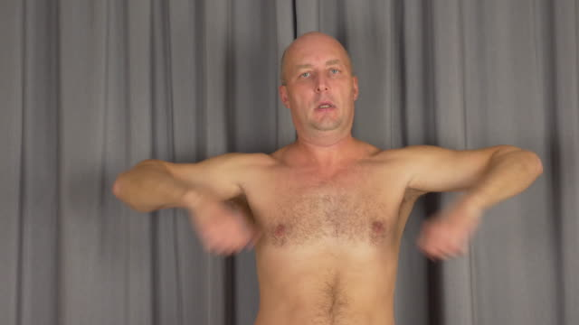 Adult caucasian man warms up shoulders muscles. Turn hands, rotates arms. video