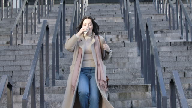 vídeos de stock e filmes b-roll de adult caucasian woman drinking coffee as running down the stairs and looking at her watch. young confident businesswoman late for meeting. cinema 4k prores hq. - important