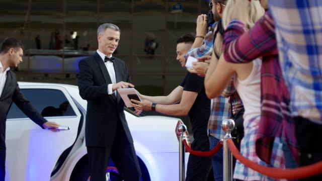 vídeos de stock, filmes e b-roll de adulta celebridades dando autógrafos no tapete vermelho - eventos de gala