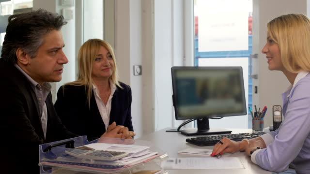 vídeos de stock, filmes e b-roll de casal adulto sentado à agência imobiliária e falar com o gerente, serviço - assistente jurídico