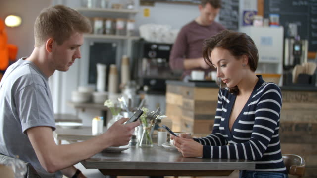 Adult couple sitting in a cafe using smartphones, close up video