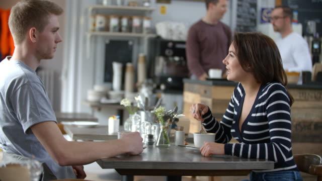 コーヒー ショップ、側面のテーブルで話している大人のカップル - 対面点の映像素材/bロール