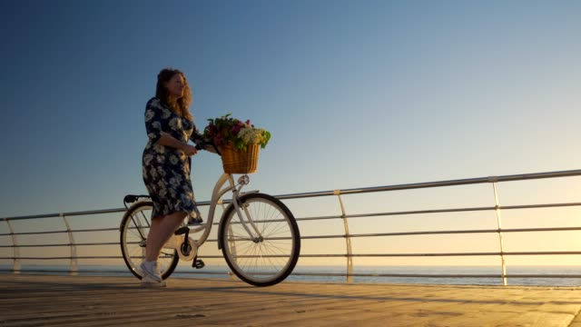 Adult cute woman with curly hair wearing dress with vintage retro white bicycle standing near sea on sunrise or sunset. Vacation travel time. Romantic scene. Feminine lifestyle. 4k