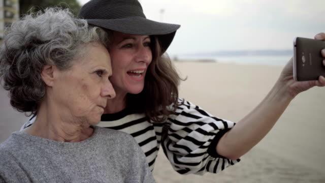 顔をゆがめたとシニアの母 selfie を取って大人の娘 ビデオ