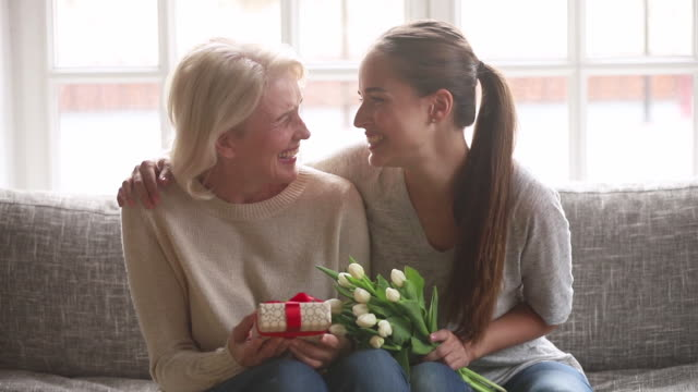 Adult daughter presenting flowers and gift box to old mother Loving adult daughter presenting spring flowers and gift box to happy old mother laughing bonding embracing, young woman congratulating hugging senior mom looking at camera on mothers day at home gifts stock videos & royalty-free footage