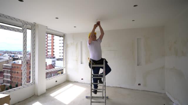 vidéos et rushes de électricien adulte sur une échelle couvrant des câbles pour installer une lampe à une amélioration de l'habitat - hlm