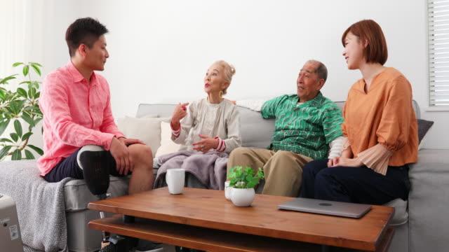 一緒に座っている大人の家族が家で話す - 息子点の映像素材/bロール