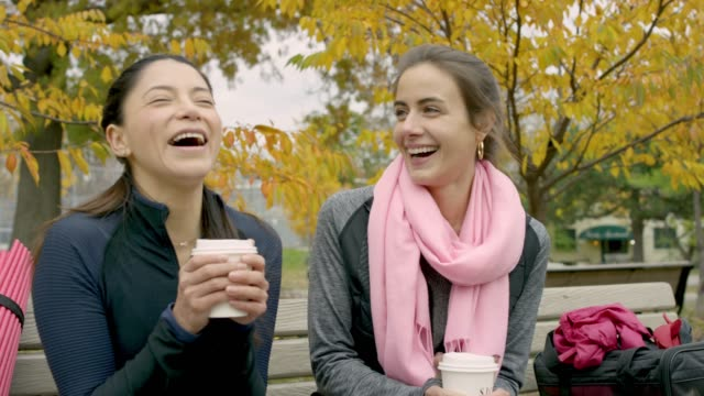 adult female friends drinking coffee on a park bench - садовая скамья стоковые видео и кадры b-roll