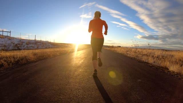 vídeos de stock e filmes b-roll de adult female running on path during late winter - passagem de ano