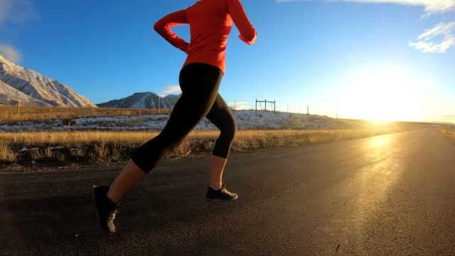 adult female running on path during late winter - potere femminile video stock e b–roll