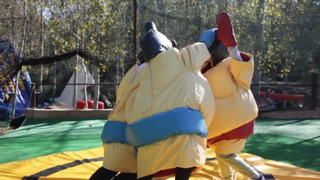 erwachsene freunde mit spaß posiert in aufblasbaren sumo-anzüge im outdoor-vergnügungspark - sumo stock-videos und b-roll-filmmaterial