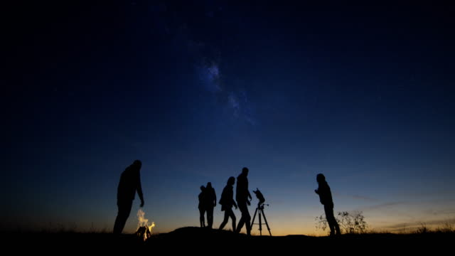 adult friends stargazing together at night - astronomia video stock e b–roll