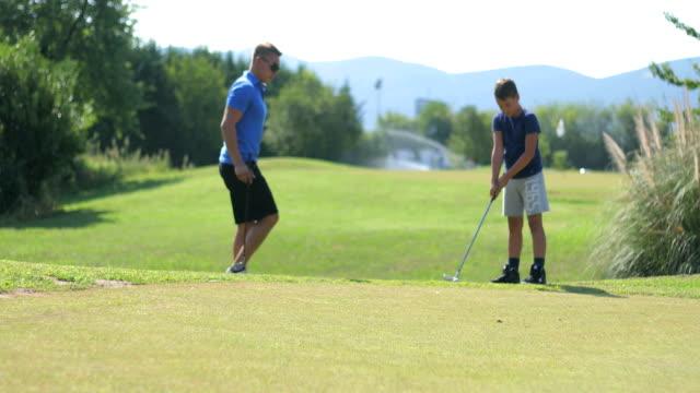 erwachsene unterrichten ein junge golfer wie man golf spielen - golf stock-videos und b-roll-filmmaterial