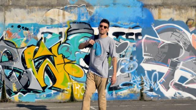 大人のグラフィティ アーティストが地面からバックパックを取ると落書きの壁を残して - street graffiti点の映像素材/bロール