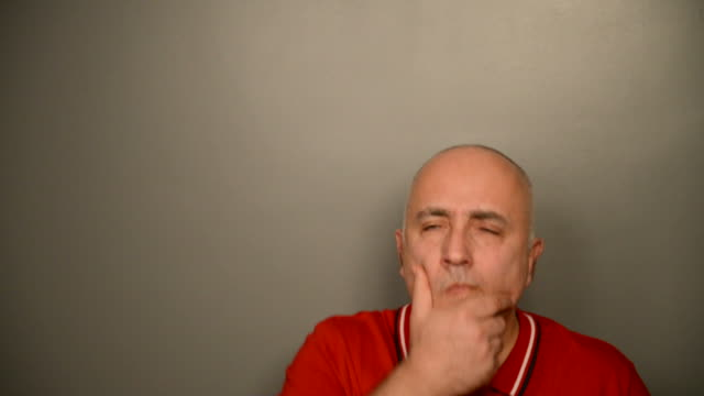 Adult gray-haired man on a gray background. The doubts. video