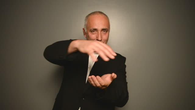 взрослый серый-светловолосую человек с деньги на сером фоне. - трюк стоковые видео и кадры b-roll