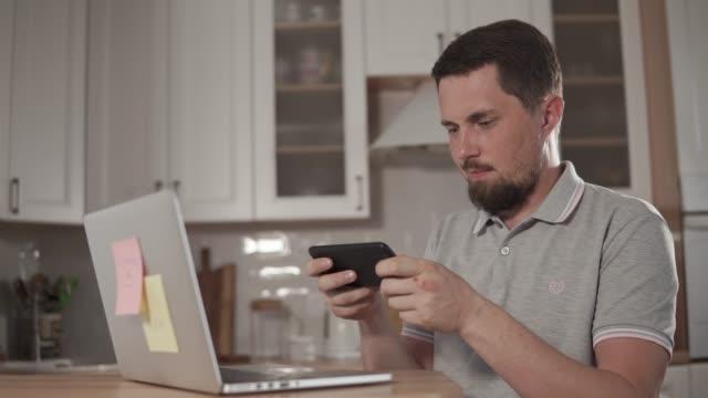 大人のハンサムな男はヘッドフォンを身に着けている家で、スマート フォンで再生します。 - ゲーム ヘッドフォン点の映像素材/bロール