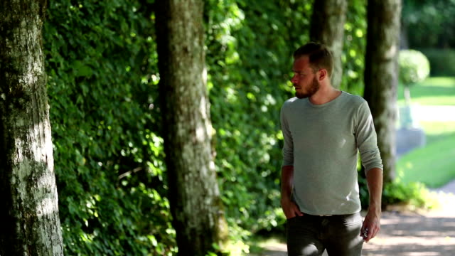 Adult in a grey shirt walking along a path outside video