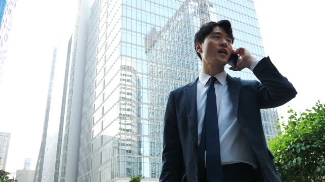 adult korean businessman using smart phone near office building - cultura coreana video stock e b–roll