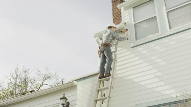 Construction de mâle adulte travailleur faisant réparation sur la résidence - Vidéo