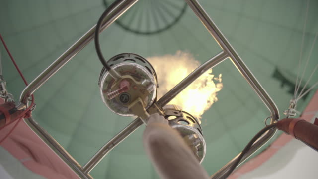 Adult male initiates burner in hot air balloon, shoots flames to heat air