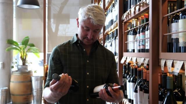 성인 남성을 찾고 와인 한 병 및 선반에 다른 옵션을 찾고 - 와인병 스톡 비디오 및 b-롤 화면