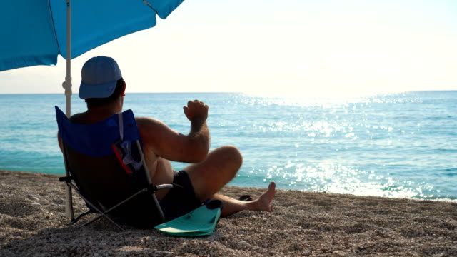 Adult male sitting on beach chair and enjoying sea view and sea breeze Adult male sitting on beach chair and enjoying sea view and sea breeze mid adult men stock videos & royalty-free footage